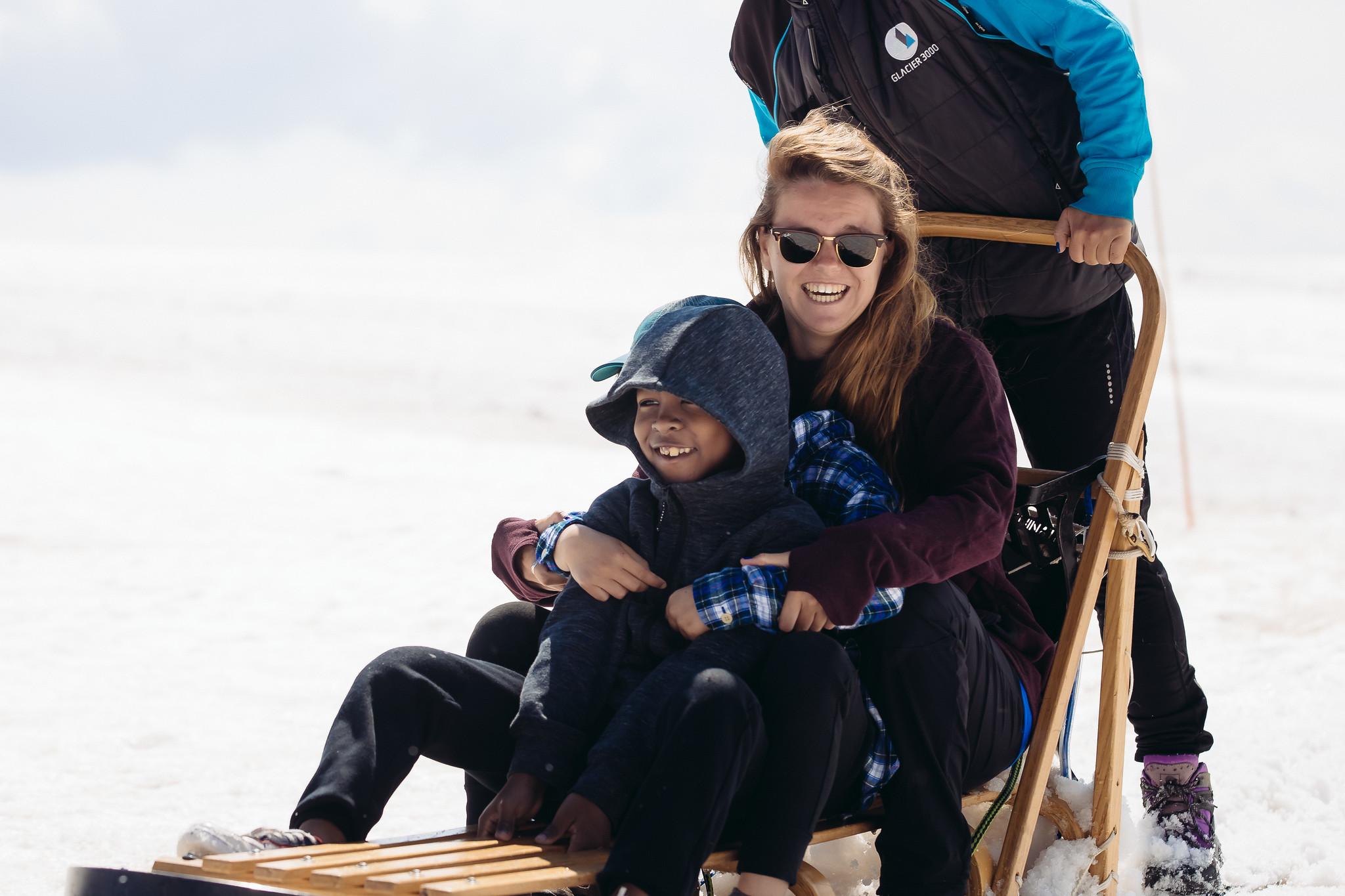 staff member and camper on husky sled