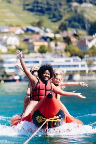group of kids on banana boat on lake geneva