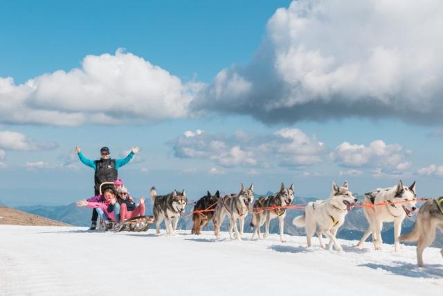 campers on sled at glacier
