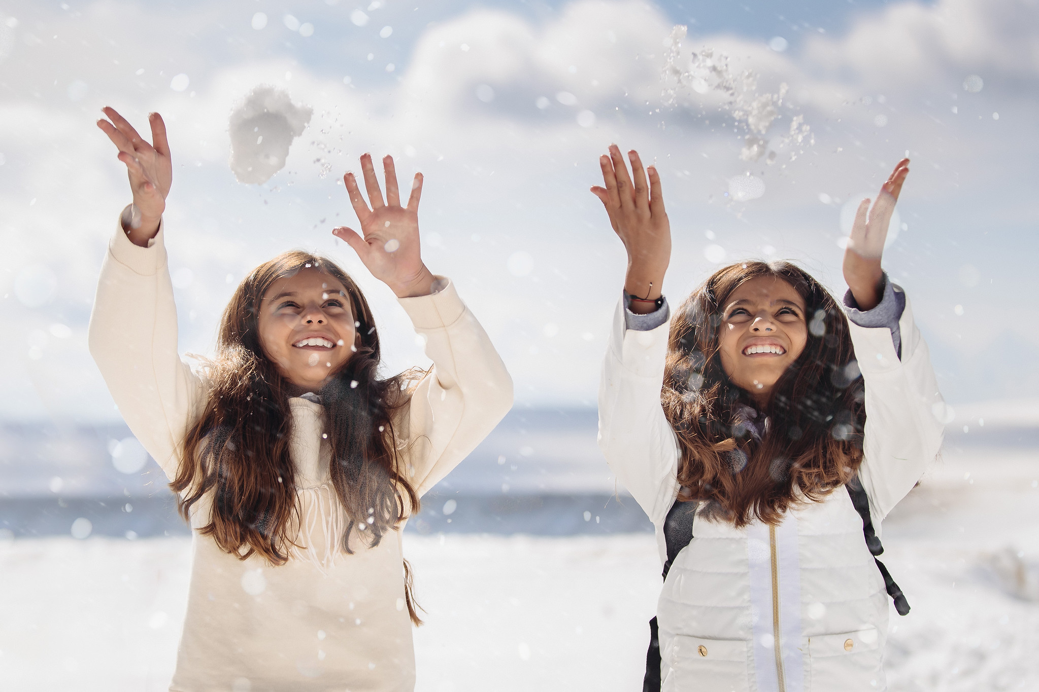two girls throwing snowballs on the glacier